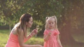 Φυσώντας πικραλίδα - ευτυχής μητέρα που παίζει με την λίγη κόρη κοριτσάκι και που έχει τη διασκέδαση - νέο καυκάσιο άσπρο mom απόθεμα βίντεο
