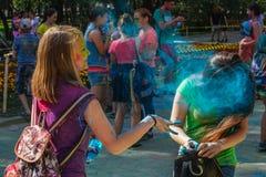 Φυσώντας σκόνη κοριτσιών στο φεστιβάλ holi χρώματος Στοκ Φωτογραφία