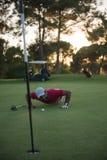 Φυσώντας σφαίρα φορέων γκολφ στην τρύπα με το ηλιοβασίλεμα στο υπόβαθρο Στοκ Εικόνες