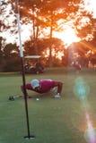 Φυσώντας σφαίρα φορέων γκολφ στην τρύπα με το ηλιοβασίλεμα στο υπόβαθρο Στοκ Φωτογραφίες
