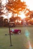 Φυσώντας σφαίρα φορέων γκολφ στην τρύπα με το ηλιοβασίλεμα στο υπόβαθρο Στοκ φωτογραφίες με δικαίωμα ελεύθερης χρήσης