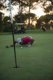 Φυσώντας σφαίρα φορέων γκολφ στην τρύπα με το ηλιοβασίλεμα στο υπόβαθρο Στοκ φωτογραφία με δικαίωμα ελεύθερης χρήσης