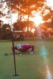 Φυσώντας σφαίρα φορέων γκολφ στην τρύπα με το ηλιοβασίλεμα στο υπόβαθρο Στοκ Φωτογραφία