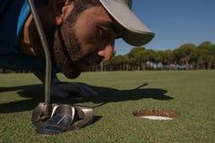 Φυσώντας σφαίρα φορέων γκολφ στην τρύπα Στοκ εικόνες με δικαίωμα ελεύθερης χρήσης