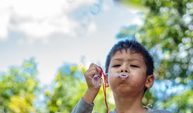 Φυσώντας φυσαλίδες αγοριών της Ασίας πορτρέτου στον κήπο στοκ φωτογραφίες