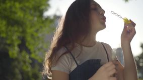 Φυσώντας φυσαλίδες σαπουνιών έφηβη στη κάμερα στο πάρκο στον ήλιο Χαριτωμένος νέος χρόνος εξόδων γυναικών μόνο υπαίθρια απόθεμα βίντεο