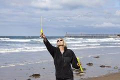 Φυσώντας φυσαλίδες σαπουνιών κοριτσιών στην παραλία στοκ φωτογραφία