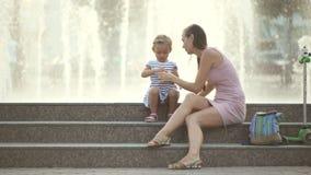 Φυσώντας φυσαλίδες μητέρων και κορών στο πάρκο απόθεμα βίντεο