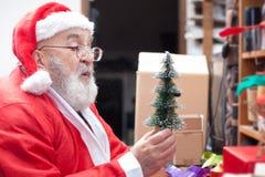 Φυσώντας χιόνι Άγιου Βασίλη στο μικροσκοπικό χριστουγεννιάτικο δέντρο Στοκ εικόνες με δικαίωμα ελεύθερης χρήσης