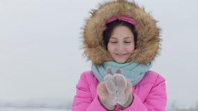 Φυσώντας χιόνι Χαρούμενο εφηβικό πρότυπο κορίτσι ομορφιάς απόθεμα βίντεο