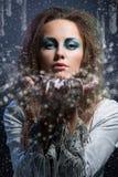 Φυσώντας snowflakes κοριτσιών Στοκ Φωτογραφία