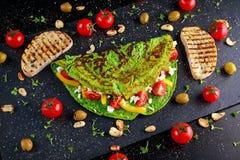 Φυτική πράσινη ομελέτα με τις ντομάτες, ελληνικό τυρί, ελιές, καρύδια, πάπρικα, φρυγανιά στο υπόβαθρο πετρών Έννοια υγιής Στοκ φωτογραφία με δικαίωμα ελεύθερης χρήσης