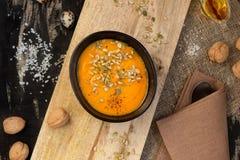 Φυτική σούπα κολοκύθας πιάτων με τους σπόρους σε έναν ξύλινο τέμνοντα πίνακα στοκ εικόνες