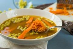 Φυτική σούπα, τεμαχισμένο και ξυμένο καρότο, μαργαριτάρι μπιζελιών, άσπρο πιάτο, κουτάλι Στοκ φωτογραφία με δικαίωμα ελεύθερης χρήσης