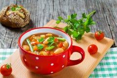 Φυτική σούπα Minestrone με τα φασόλια, κουνουπίδι, ντομάτες, κινηματογράφηση σε πρώτο πλάνο, τοπ άποψη Στοκ Εικόνες