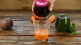 Φυτικός χυμός τρία στο φλυτζάνι γυαλιού σε ξύλινο απόθεμα βίντεο