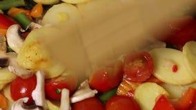Φυτικό μίγμα με τα μανιτάρια που τηγανίζονται σε ένα τηγάνι απόθεμα βίντεο