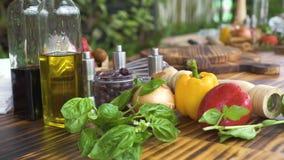 Φυτικό υπόβαθρο ξύλινο επιτραπέζιο στενό σε επάνω κουζινών Φρέσκο λαχανικό, χορτάρι βασιλικού, ελαιόλαδο, που καρυκεύει για απόθεμα βίντεο