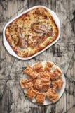 Φυτικό Stew κοτόπουλου στο τηγάνι ψησίματος με Plateful τσαλακωμένων των Gibanica φετών πιτών τυριών στον παλαιό ραγισμένο λεπιοε Στοκ Εικόνες