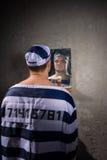 0 φυλακισμένος που στέκεται και που εξετάζει την αντανάκλασή του στο mir Στοκ Εικόνες