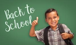 Φυλλομετρεί επάνω το ισπανικό αγόρι μπροστά από πίσω στον πίνακα σχολικής κιμωλίας Στοκ φωτογραφίες με δικαίωμα ελεύθερης χρήσης