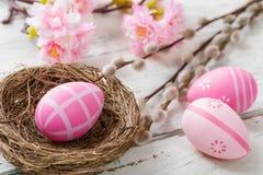 Φωλιά Πάσχας με τα ρόδινα αυγά Πάσχας σε ένα ξύλινο υπόβαθρο Στοκ Εικόνες