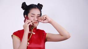 Φωνάζοντας ένδυση γυναικών cheongsam και χρησιμοποίηση του κινητού τηλεφώνου απόθεμα βίντεο