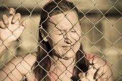 Φωνάζοντας γυναίκα Devastatetd στο φράκτη φυλακών Στοκ φωτογραφία με δικαίωμα ελεύθερης χρήσης