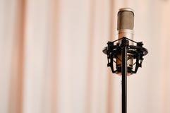 Μικρόφωνο που στέκεται πέρα από τη ρόδινη κουρτίνα Στοκ φωτογραφία με δικαίωμα ελεύθερης χρήσης