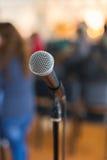 Φωνητικό μικρόφωνο στην εστίαση ενάντια στο θολωμένο ακροατήριο στη διάσκεψη Στοκ Εικόνα