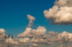 Φως λαμπτήρων οδών και μέρος των σύννεφων σε έναν μπλε ουρανό με τα άσπρα σύννεφα Στοκ Εικόνες