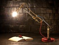 Φως από έναν καυστήρα αερίου στον πίνακα δίπλα στο μαύρο βιβλίο   Στοκ Εικόνες
