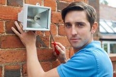 Φως ασφάλειας συναρμολογήσεων ατόμων στον τοίχο σπιτιών Στοκ εικόνες με δικαίωμα ελεύθερης χρήσης
