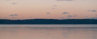 Φως ηλιοβασιλέματος πέρα από την παγωμένη λίμνη Στοκ Εικόνα
