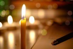 Φως κεριών με το θολωμένο υπόβαθρο βιβλίων στην εκκλησία Στοκ εικόνες με δικαίωμα ελεύθερης χρήσης