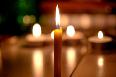 Φως κεριών με το θολωμένο υπόβαθρο βιβλίων στην εκκλησία Στοκ Φωτογραφία