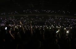Φως λάμψης από ένα κινητό τηλέφωνο σε μια συναυλία μουσικής στοκ φωτογραφίες