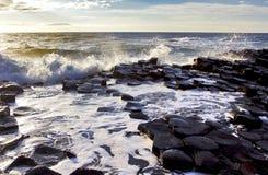 Φως του ήλιου που δίνει έμφαση στα κύματα που συντρίβουν επάνω στις εξαγωνικές πλάκες βασαλτών του υπερυψωμένου μονοπατιού γιγάντω Στοκ Φωτογραφία