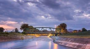 Φωτίστε, γέφυρα σιδηροδρόμου μετάλλων πέρα από θολωμένο το κίνηση πανόραμα ποταμών στοκ φωτογραφία με δικαίωμα ελεύθερης χρήσης