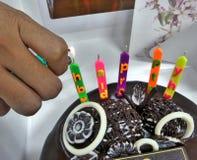 Φωτίστε τα ζωηρόχρωμα κεριά cerebration στο κέικ και το μπισκότο σοκολάτας στο άσπρο υπόβαθρο στοκ εικόνες
