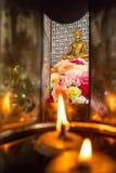 Φωτίστε τα κεριά και τα όμορφα ζωηρόχρωμα λουλούδια για να λατρεψετε χρυσό στοκ εικόνες με δικαίωμα ελεύθερης χρήσης