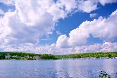 Φωτεινά άσπρα σύννεφα στο μπλε ουρανό πέρα από το σιβηρικό ποταμό Angara κόλπων Στοκ Εικόνες