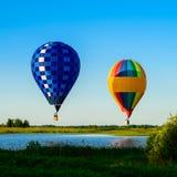 Φωτεινά ζωηρόχρωμα μπαλόνια ζεστού αέρα που πετούν πέρα από τη λίμνη στο σαφές β Στοκ φωτογραφίες με δικαίωμα ελεύθερης χρήσης