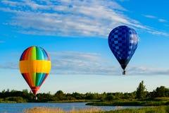 Φωτεινά ζωηρόχρωμα μπαλόνια ζεστού αέρα που πετούν πέρα από τη λίμνη στο σαφές β Στοκ Φωτογραφία