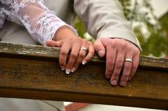 Φωτεινά και χέρια του νεόνυμφου με τα γαμήλια δαχτυλίδια Στοκ Εικόνα