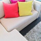 Φωτεινά μαξιλάρια στον γκρίζο καναπέ γωνιών Στοκ Φωτογραφία