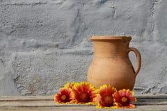 Φωτεινά λουλούδια κοντά στην παλαιά κεραμική κανάτα Στοκ φωτογραφία με δικαίωμα ελεύθερης χρήσης