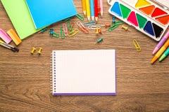 Φωτεινά σχολικά εξαρτήματα, χαρτικά σε ένα ξύλινο υπόβαθρο επάνω από την όψη στοκ φωτογραφία