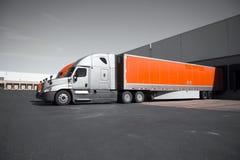 Φωτεινά σύγχρονα πορτοκαλιά και γκρίζα ημι φορτηγά που ξεφορτώνουν στην αποθήκη εμπορευμάτων Στοκ Φωτογραφία
