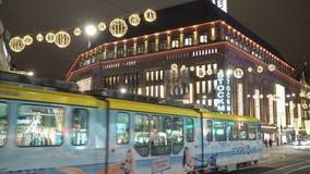 Φωτεινά τραμ στις κεντρικές οδούς στο Ελσίνκι κατά τη διάρκεια των Χριστουγέννων Πολλοί άνθρωποι, πωλήσεις διακοπών και φωτεινές  απόθεμα βίντεο